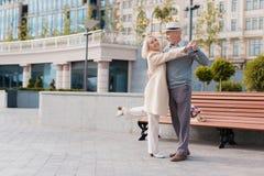 2 пенсионера танцуют на квадрате около стенда Они счастливы Стоковая Фотография