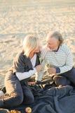Пенсионеры выпивая шампанское и сидя на шотландке на пляже песка стоковое фото