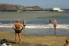 Пенсионеры ослабляют на песчаном пляже и заливе на Playa Las Америках при прибой ломая на бечевнике стоковая фотография rf