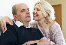 Пенсионеры пар совместно на софе дома стоковое изображение