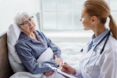 Пенсионер практикующий врача рассматривая в белом офисе больницы Стоковые Изображения