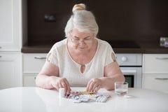 Пенсионер сидит на таблице и смотрит его лекарство стоковое изображение