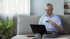 Пенсионер сидя на софе и вводя номер карты на компьтер-книжку, онлайн покупки стоковые фото