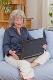 Пенсионер с компьтер-книжкой на софе Стоковое Изображение RF