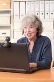 Пенсионер телефонируя через skype Стоковое Изображение