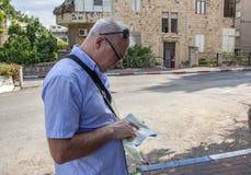 Пенсионный возраст путешественника смотря в туристскую карту стоковое фото rf