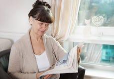 Пенсионный возраст хороший смотрящ женщину читая газету Стоковое фото RF