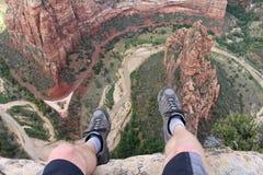 Первая перспектива персоны сняла от hiker сидя на крае скалы в национальном парке Сиона Стоковые Изображения RF