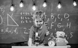 Первое бывшее заинтересованное в изучать, учащ, образование Оягнитесь мальчик около микроскопа в классе, доске на предпосылке стоковая фотография