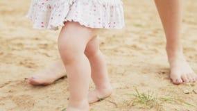 Первое ` s младенца шагает на песчаный пляж сток-видео
