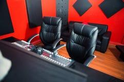 Первоклассная профессиональная установка студии звукозаписи, большой стол с смешивая консолью и 2 стуль, окно для вокальной будоч Стоковые Изображения RF