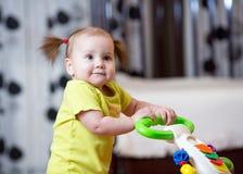 Первые шаги девушки маленького ребенка в ходоке младенца стоковая фотография rf