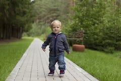 Первые шаги ` s младенца Первые независимые шаги Идущий малыш в парке Стоковое Фото