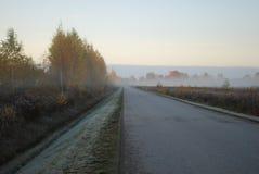 Первый заморозок, туман в утре осени на дороге Стоковая Фотография RF