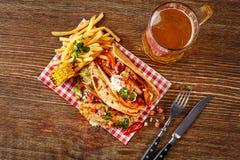 Первый tortilla мозоли с зажаренным филе цыпленка, второе с филе рыб, соус и пиво на деревянном столе Взгляд сверху Стоковые Фото