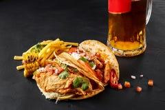 Первый tortilla мозоли с зажаренным филе цыпленка, второе с филе рыб, французские фраи, соус и пиво на черноте Стоковое Фото