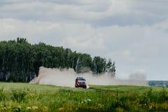 перевезите автомобиль на грузовиках Renault ралли управляя на дороге пыли среди леса и травы Стоковое фото RF