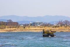 Перевезите на грузовиках и драгируя камень в реке Katsura для для того чтобы сделать воду пропустить оно ` s легкое в Киото стоковое изображение