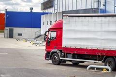 Перевезите на грузовиках около центра снабжения на разгржать или нагружать груза в транспорт контейнера концепции товаров около п стоковые фотографии rf