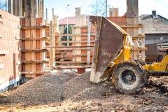 Перевезите разгржать на грузовиках гравий с экскаватором и backhoe на строительной площадке стоковые фотографии rf