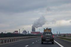 Перевезите управлять на грузовиках на румынском шоссе около дороги Sebes, сильно загрязняя фабрика обработки древесины смогите бы Стоковое Фото