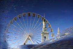 Перевернутое отражение в лужице Колесо Ferris на предпосылке колокольни и голубого неба Киев, Украин стоковое изображение