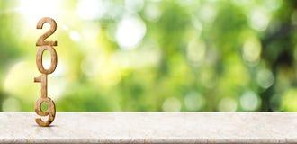 Перевод номера 3d Нового Года 2019 деревянный на мраморной таблице на bokeh нерезкости абстрактном зеленом с предпосылкой луча со стоковое изображение rf