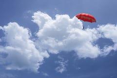 перевод 3D: иллюстрация красного зонтика плавая выше против голубого неба и облаков Дело, концепция руководителя, был другой Стоковые Фото