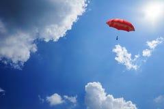 перевод 3D: иллюстрация красного зонтика плавая выше против голубого неба и облаков Дело, концепция руководителя, был другой Стоковая Фотография