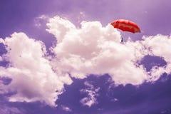 перевод 3D: иллюстрация красного зонтика плавая выше против голубого неба и облаков Дело, концепция руководителя, был другой Стоковое фото RF