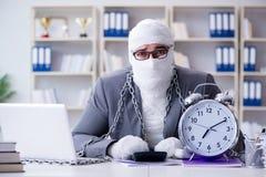 Перевязанный работник бизнесмена работая в офисе делая paperwor Стоковое Изображение