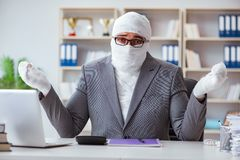Перевязанный работник бизнесмена работая в офисе делая paperwor Стоковые Изображения