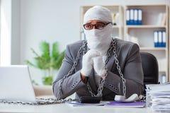 Перевязанный работник бизнесмена работая в офисе делая paperwor Стоковое Фото