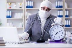 Перевязанный работник бизнесмена работая в офисе делая paperwor Стоковое Изображение RF
