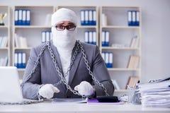 Перевязанный работник бизнесмена работая в офисе делая paperwor Стоковая Фотография RF