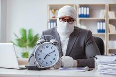 Перевязанный работник бизнесмена работая в офисе делая paperwor Стоковые Фото
