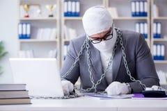 Перевязанный работник бизнесмена работая в офисе делая paperwor Стоковое фото RF