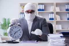 Перевязанный работник бизнесмена работая в офисе делая paperwor Стоковые Изображения RF