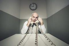 Перегружанный бизнесмен на телефоне стоковое фото