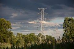 Передающие линии решетки энергетической промышленности электрические возвышаются электричество поставки стоковые фото