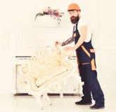 Передислоцировать концепцию Курьер поставляет мебель в случае двигает вне, перестановка Человек с бородой, работник в прозодеждах стоковые фото