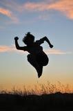 передние высокие прыжки укомплектовывают личным составом заход солнца Стоковая Фотография