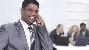 Передний план бизнесмена говоря на мобильном телефоне в  Стоковое Фото