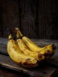 3 перезрелых банана на темной деревянной предпосылке Стоковая Фотография RF