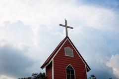 Перекрестная церковь с красным зданием и голубым небом   Христианские место и символ вероисповедания Стоковая Фотография