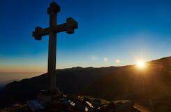 Перекрестный знак на пропуске горного пика на заход солнца Стоковые Изображения RF