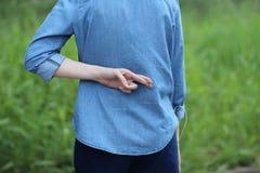 Перекрестный палец на задней части голубого демикотона Стоковые Изображения RF