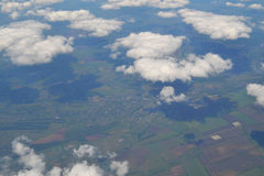 Перемещать воздухом Взгляд через окно самолета Облака цирруса и кумулюса и меньшее завихрение, показывая ` s земли Стоковая Фотография RF