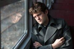 Перемещать поездом Унылый человек путешествуя поездом, смотря через окно и думая о сжимать неоплаченной влюбленности Стоковое Изображение RF