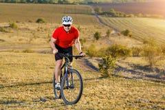 Перемещение велосипедиста туристское на горном велосипеде Ландшафт осени Спортсмен на велосипеде в красном jersey и белом шлеме Стоковые Фотографии RF